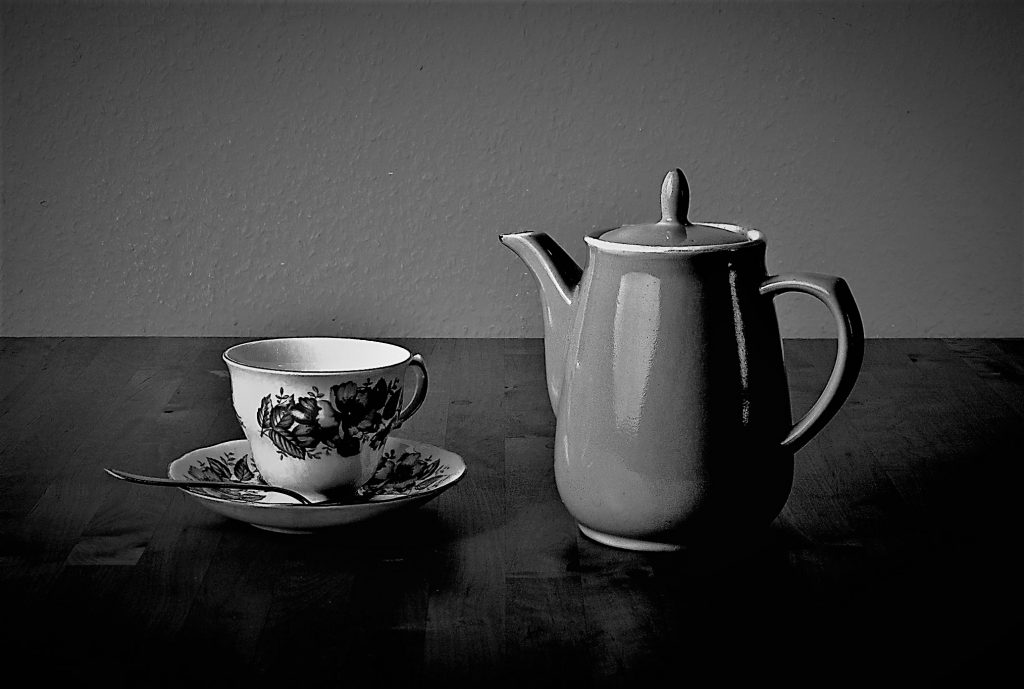 Still Life Photograph of a tea pot and a tea cup with saucer. Black and white, simple composition with dark tones